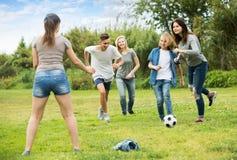 Amis d'adolescents courant avec la boule Images stock