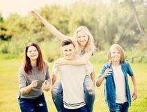 Amis d'adolescents courant sur le pré Image stock