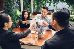 Amis d'affaires encourageant avec du café au café Photographie stock libre de droits