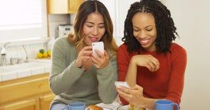 Amis d'afro-américain et d'Asiatique à l'aide des téléphones portables et mangeant le petit déjeuner Images stock