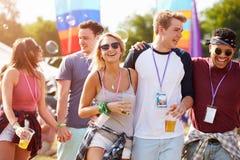 Amis d'amis marchant par un site de festival de musique Image stock