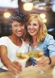 Amis d'amusement célébrant avec du vin blanc Images libres de droits