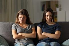 Amis d'Anfry s'ignorant à la maison pendant la nuit Images stock