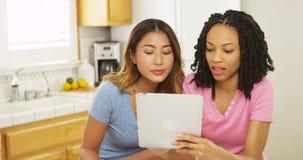 Amis d'Asiatique et d'Afro-américain à l'aide de la tablette dans la cuisine Photo libre de droits