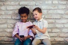 Amis d'enfants de diversité employant le concept de dispositifs de Digital photos libres de droits