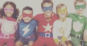 Amis d'enfants de super héros jouant le concept d'amusement d'unité Photographie stock