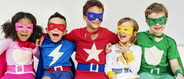 Amis d'enfants de super héros jouant le concept d'amusement d'unité Images libres de droits
