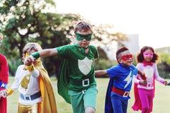 Amis d'enfants de super héros jouant le concept d'amusement d'unité Images stock