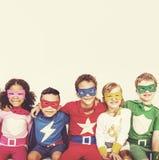 Amis d'enfants de super héros jouant le concept d'unité Photo stock