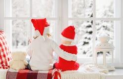 Amis d'enfants s'asseyant de retour dans Noël de fenêtre d'hiver Photographie stock