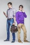 Amis d'hommes avec des smartphones dans les mains Images stock