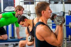 Amis d'hommes de forme physique dans des poids de séance d'entraînement de gymnase avec l'équipement Image libre de droits