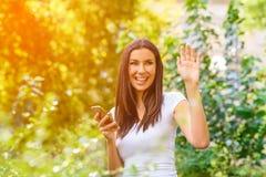 Amis d'une salutation de jeune femme tout en à l'aide de son smartphone dans un P Image stock