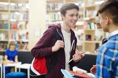 Amis d'université parlant dans la bibliothèque Photographie stock libre de droits