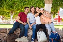 Amis d'université prenant le selfie Image stock