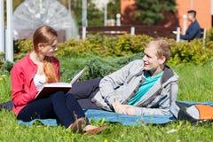 Amis d'université s'asseyant sur l'herbe Photographie stock libre de droits