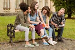 Amis d'université s'asseyant sur le banc dans le campus Photo stock