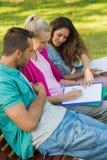 Amis d'université s'asseyant sur le banc de campus Photos libres de droits