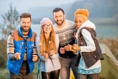 Amis dans des chandails célébrant au camping Image libre de droits