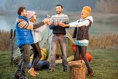 Amis dans des chandails célébrant au camping Image stock
