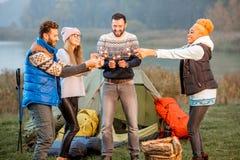 Amis dans des chandails célébrant au camping Images stock
