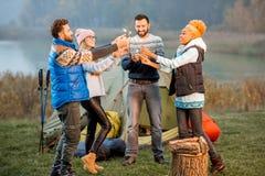 Amis dans des chandails célébrant au camping Photographie stock libre de droits