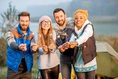 Amis dans des chandails célébrant au camping Photographie stock