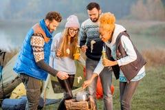 Amis dans des chandails mangeant la fondue dehors Images libres de droits