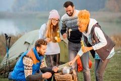 Amis dans des chandails mangeant la fondue dehors Image libre de droits