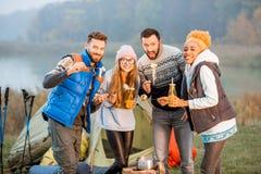 Amis dans des chandails mangeant la fondue dehors Image stock