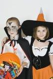 Amis dans des costumes de Halloween se tenant ensemble Photographie stock