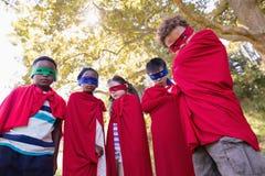 Amis dans des costumes de super héros se tenant au terrain de camping Image libre de droits