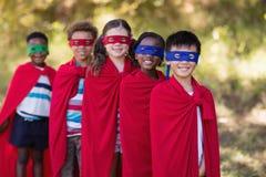 Amis dans des costumes de super héros se tenant au terrain de camping Images libres de droits