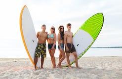 Amis dans des lunettes de soleil avec des planches de surf sur la plage Photographie stock libre de droits