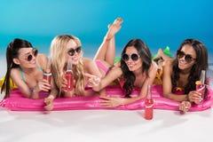Amis dans des lunettes de soleil buvant des cocktails tout en se trouvant sur les matelas de natation Photographie stock