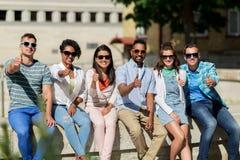 Amis dans des lunettes de soleil dans la ville montrant des pouces  Photographie stock