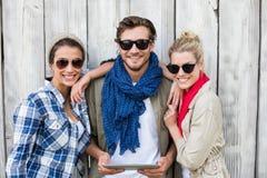 Amis dans des lunettes de soleil utilisant le comprimé numérique Photos stock