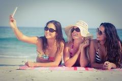 Amis dans des maillots de bain prenant un selfie Image libre de droits