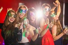 Amis dans des masques de mascarade buvant du champagne Photo libre de droits