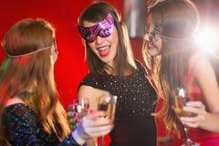 Amis dans des masques de mascarade buvant du champagne Photographie stock libre de droits