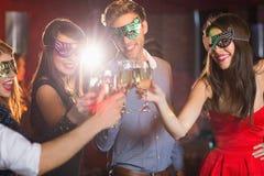 Amis dans des masques de mascarade grillant avec le champagne Photos libres de droits