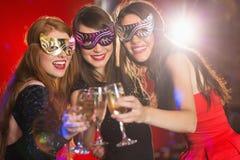 Amis dans des masques de mascarade grillant avec le champagne Image stock
