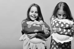 Amis dans des pyjamas roses d'isolement sur le fond rose Les filles avec les cheveux lâches étreignent leurs oreillers Enfance et Photo stock