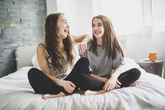 Amis dans des pyjamas se reposant dans le lit à la maison détendant Photo libre de droits