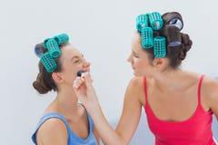 Amis dans des rouleaux de cheveux ayant l'amusement avec le maquillage Images libres de droits
