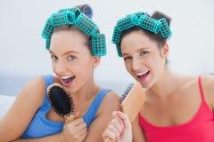 Amis dans des rouleaux de cheveux chantant dans leurs brosses à cheveux Photographie stock libre de droits