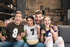 Amis dans des T-shirts buvant de la bière et mangeant du maïs éclaté Photos libres de droits