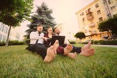 amis dans des vêtements d'affaires et se reposer nu-pieds sur l'herbe tenant l'ordinateur portable dans des mains Image stock