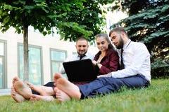 amis dans des vêtements d'affaires et se reposer nu-pieds sur l'herbe tenant l'ordinateur portable dans des mains Images stock