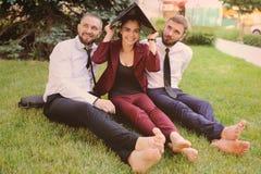 amis dans des vêtements d'affaires et se reposer nu-pieds sur l'herbe tenant l'ordinateur portable dans des mains Image libre de droits